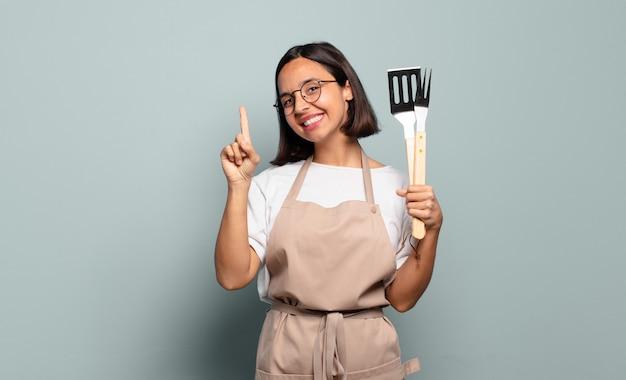 Jonge spaanse vrouw lacht en ziet er vriendelijk uit, toont nummer één of eerst met de hand naar voren, aftellend