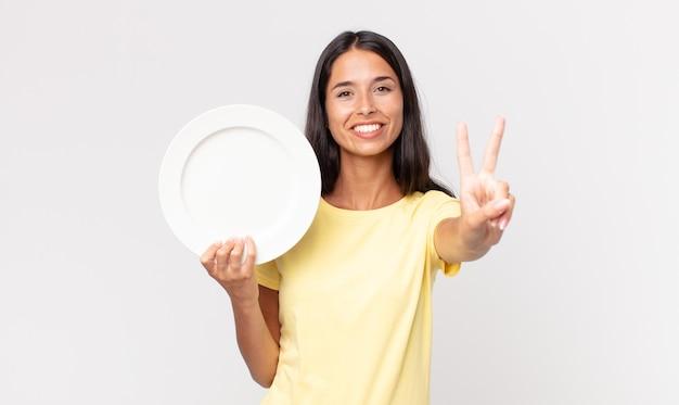 Jonge spaanse vrouw lacht en ziet er vriendelijk uit, toont nummer twee en houdt een leeg bord vast