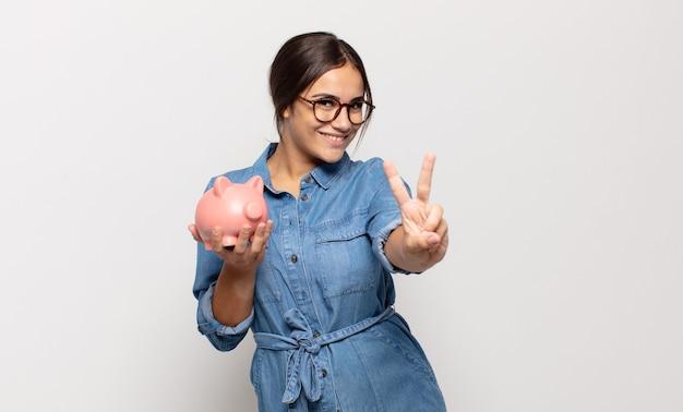 Jonge spaanse vrouw lacht en ziet er vriendelijk uit, toont nummer twee of seconde met de hand naar voren, aftellend