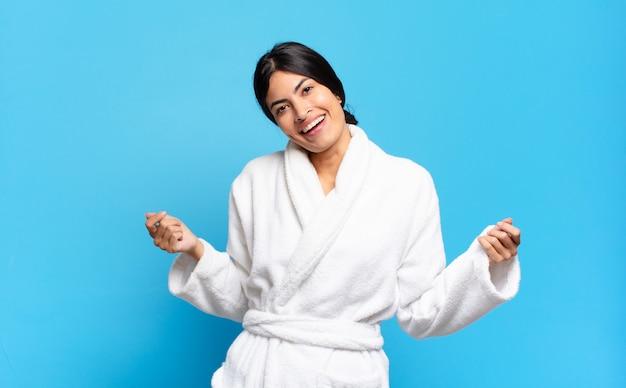 Jonge spaanse vrouw lacht, voelt zich zorgeloos, ontspannen en gelukkig, danst en luistert naar muziek, plezier op een feestje. badjas concept