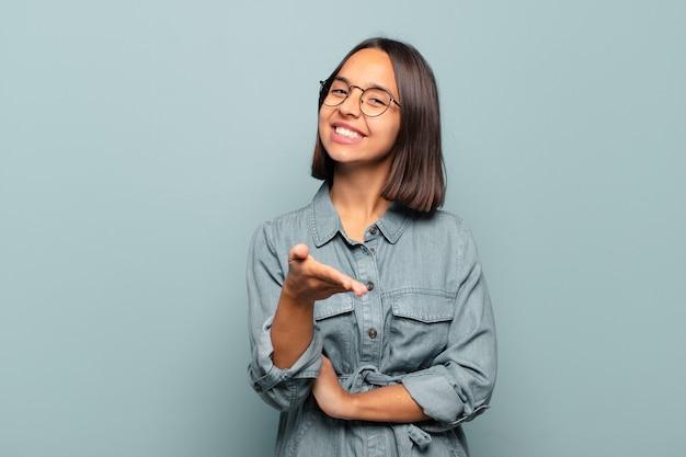 Jonge spaanse vrouw lacht, ziet er gelukkig, zelfverzekerd en vriendelijk uit, biedt een handdruk om een deal te sluiten, samen te werken