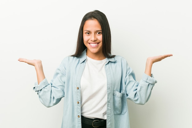 Jonge spaanse vrouw maakt schaal met armen, voelt zich gelukkig en zelfverzekerd.