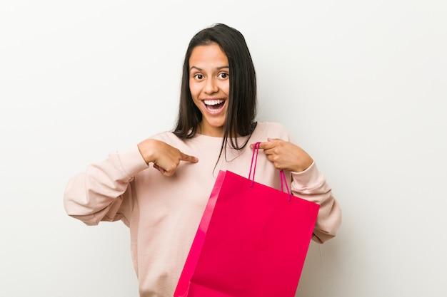 Jonge spaanse vrouw met een boodschappentas verrast wijzend op zichzelf, breed lachend
