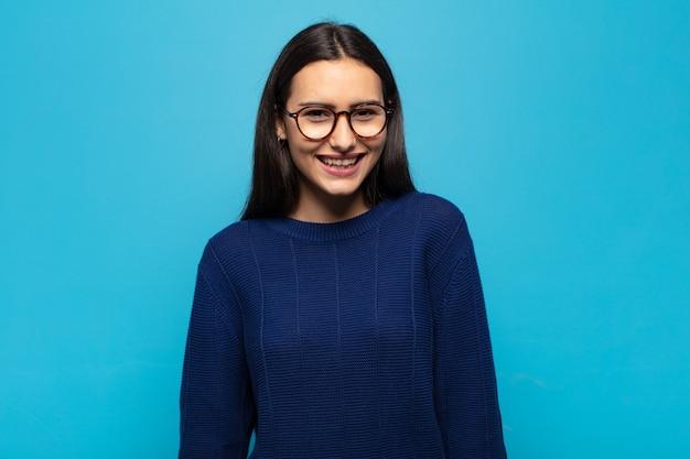 Jonge spaanse vrouw met een grote, vriendelijke, zorgeloze glimlach, die er positief, ontspannen en gelukkig uitziet, huiveringwekkend