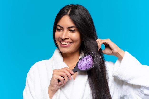 Jonge spaanse vrouw met een haarborstel.