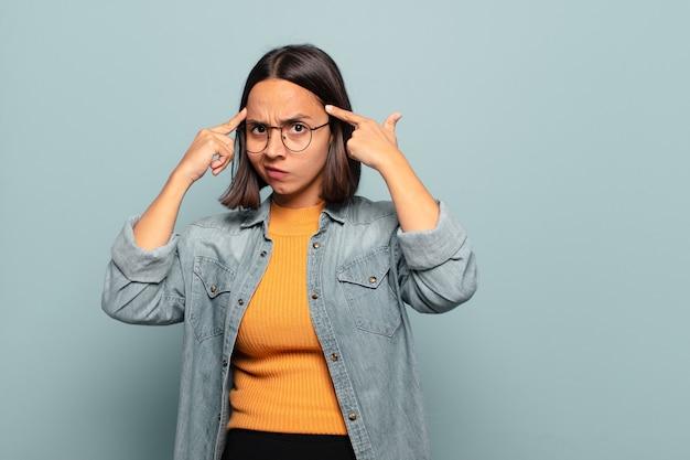 Jonge spaanse vrouw met een serieuze en geconcentreerde blik, die brainstormt en nadenkt over een uitdagend probleem