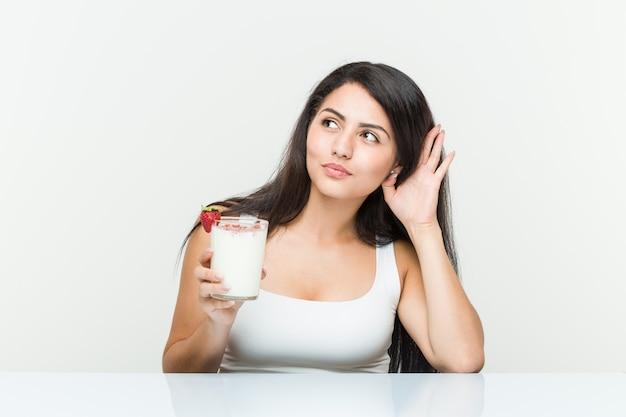 Jonge spaanse vrouw met een smoothie jonge spaanse vrouw met een avocadotoost proberen te luisteren naar een roddel. <mixto>