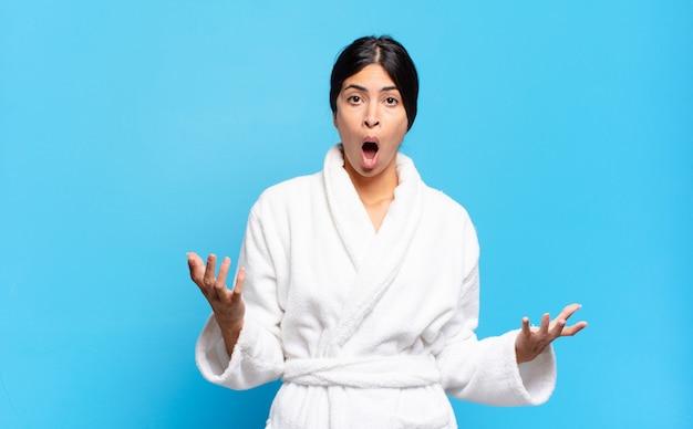 Jonge spaanse vrouw met open mond en verbaasd, geschokt en verbaasd met een ongelooflijke verrassing. badjas concept