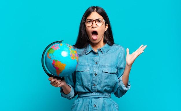 Jonge spaanse vrouw met open mond en verbaasd, geschokt en verbaasd over een ongelooflijke verrassing