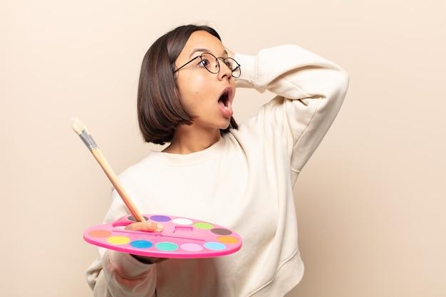 Jonge spaanse vrouw met open mond, geschokt en geschokt vanwege een vreselijke fout, handen opstekend