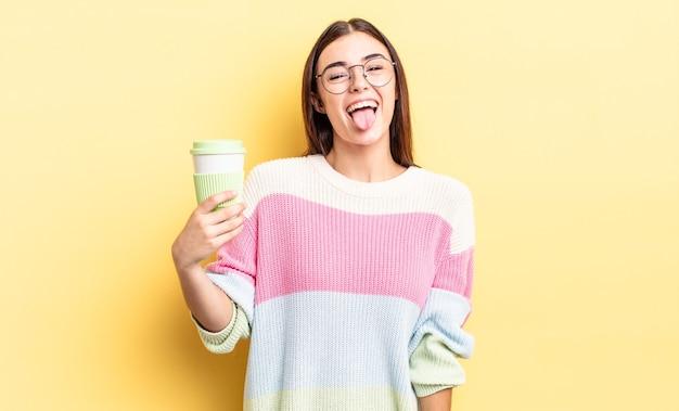 Jonge spaanse vrouw met vrolijke en rebelse houding, grappen maken en tong uitsteken. afhaal koffie concept