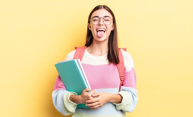 Jonge spaanse vrouw met vrolijke en rebelse houding, grappen maken en tong uitsteken. studentenconcept