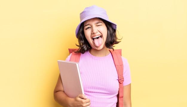 Jonge spaanse vrouw met vrolijke en rebelse houding, grappen maken en tong uitsteken. terug naar schoolconcept