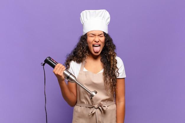 Jonge spaanse vrouw met vrolijke, zorgeloze, rebelse houding, grappen maken en tong uitsteken, plezier maken. chef-kok concept