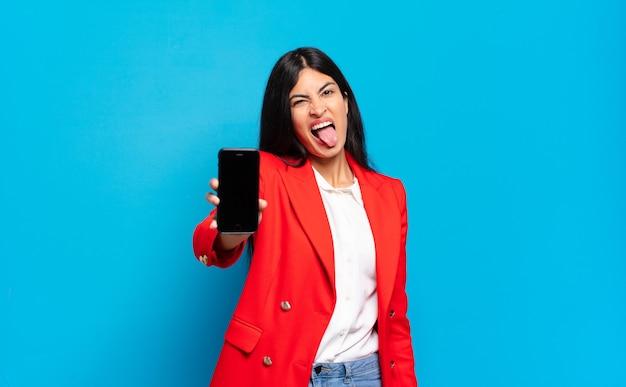Jonge spaanse vrouw met vrolijke, zorgeloze, rebelse houding, grappen maken en tong uitsteken, plezier maken, kopie ruimte telefoonscherm