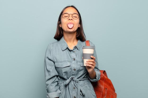 Jonge spaanse vrouw met vrolijke, zorgeloze, rebelse houding, grappen maken en tong uitsteken, plezier maken