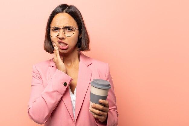 Jonge spaanse vrouw met wang en pijnlijke kiespijn, zich ziek, ellendig en ongelukkig voelen, op zoek naar een tandarts