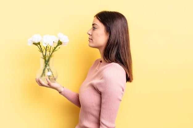 Jonge spaanse vrouw op profielweergave denken, verbeelden of dagdromen. bloempot concept