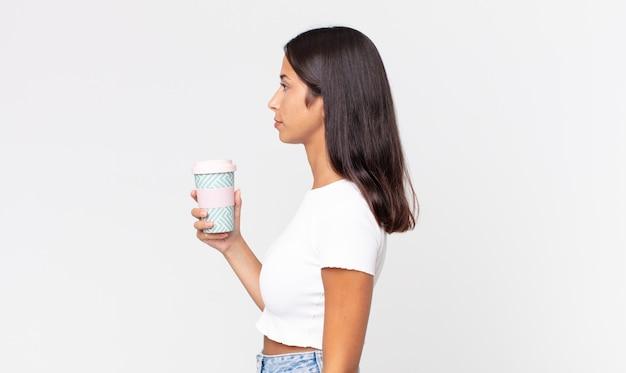 Jonge spaanse vrouw op profielweergave denken, verbeelden of dagdromen en een afhaalkoffiecontainer vasthouden
