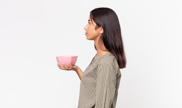 Jonge spaanse vrouw op profielweergave denken, verbeelden of dagdromen en een lege kom of pot vasthouden