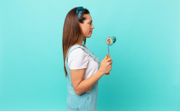 Jonge spaanse vrouw op profielweergave denken, verbeelden of dagdromen en een muur schilderen