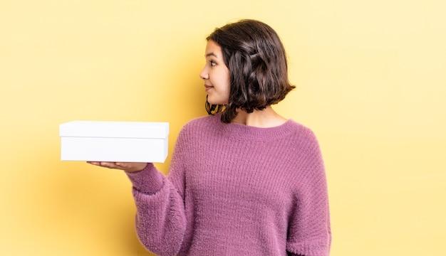 Jonge spaanse vrouw op profielweergave denken, verbeelden of dagdromen. lege doos concept