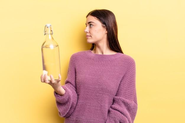 Jonge spaanse vrouw op profielweergave denken, verbeelden of dagdromen. waterfles concept