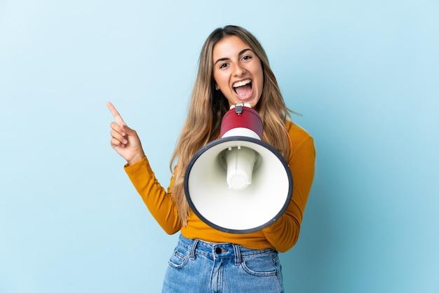 Jonge spaanse vrouw over geïsoleerde blauwe achtergrond die door een megafoon schreeuwt en naar de zijkant wijst