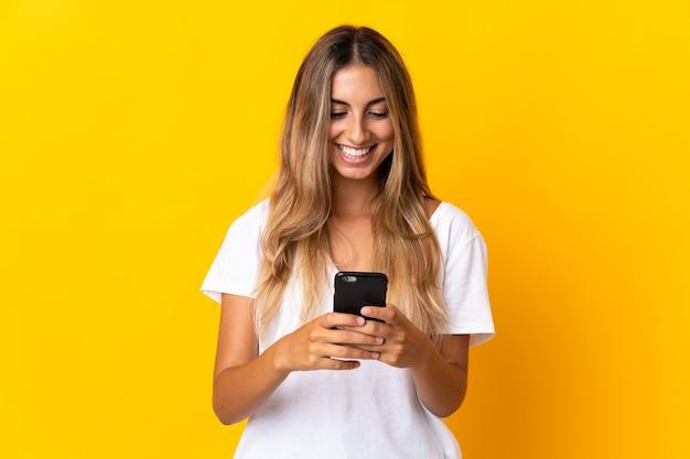 Jonge spaanse vrouw over geïsoleerde gele muur die een bericht of e-mail met mobiel verzendt
