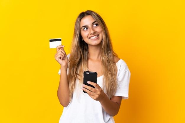 Jonge spaanse vrouw over geïsoleerde gele muur die met mobiel met een creditcard koopt terwijl het nadenken