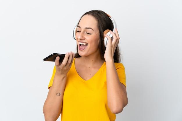 Jonge spaanse vrouw over geïsoleerde witte muur het luisteren muziek met gsm en het zingen