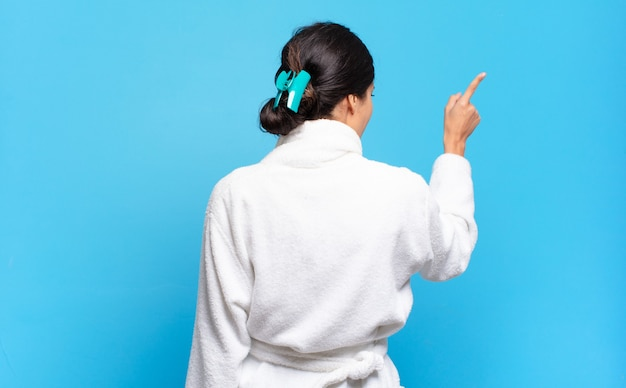 Jonge spaanse vrouw permanent en wijst naar bezwaar op kopie ruimte, achteraanzicht. badjas concept