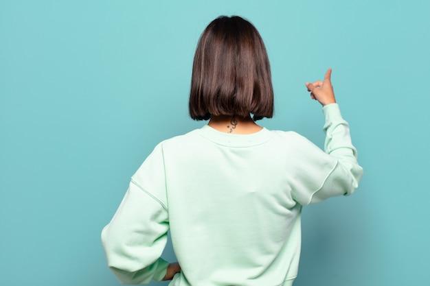 Jonge spaanse vrouw permanent en wijst naar bezwaar op kopie ruimte, achteraanzicht
