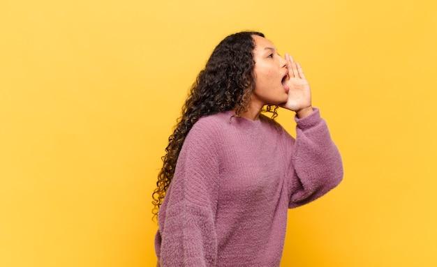 Jonge spaanse vrouw profielweergave, blij en opgewonden kijkend, schreeuwend en bellend om ruimte aan de zijkant te kopiëren