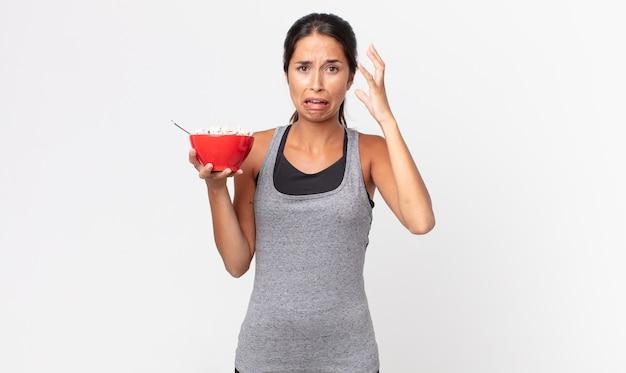 Jonge spaanse vrouw schreeuwen met handen omhoog in de lucht. fitness dieet en ontbijt concept