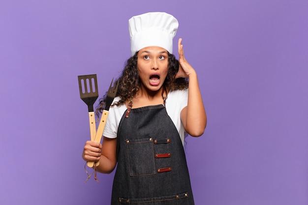 Jonge spaanse vrouw schreeuwt met handen in de lucht, voelt zich woedend, gefrustreerd, gestrest en overstuur. barbecue chef-kok concept