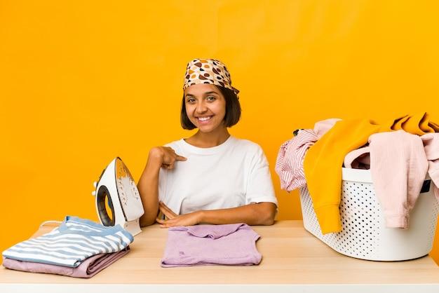 Jonge spaanse vrouw strijken van kleren geïsoleerde persoon die met de hand naar een overhemds kopie ruimte, trots en zelfverzekerd
