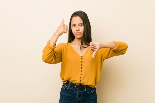 Jonge spaanse vrouw tegen een beige achtergrond met duimen omhoog en duimen omlaag
