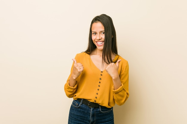 Jonge spaanse vrouw tegen een beige die beide duimen opheft, glimlachend en zelfverzekerd.