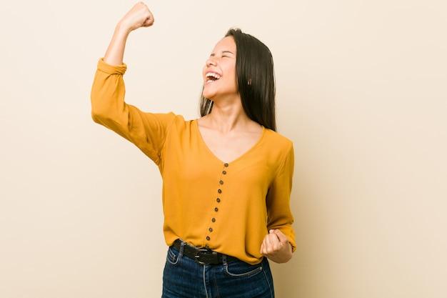 Jonge spaanse vrouw tegen een beige muur die vuist na een overwinning opheft, winnaarconcept.