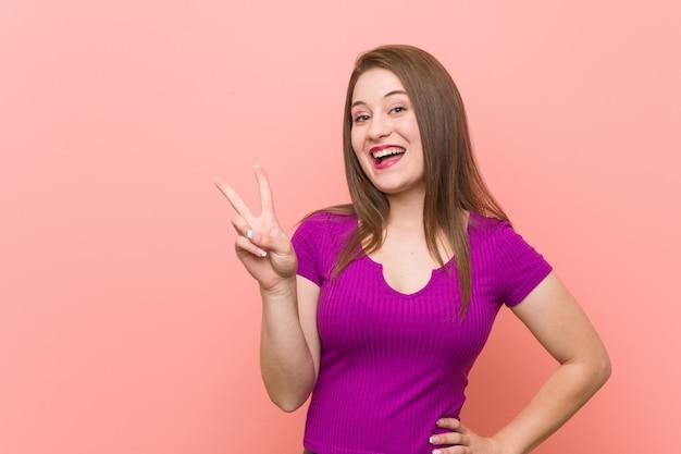Jonge spaanse vrouw tegen een roze overwinningsteken tonen en breed die glimlachen.