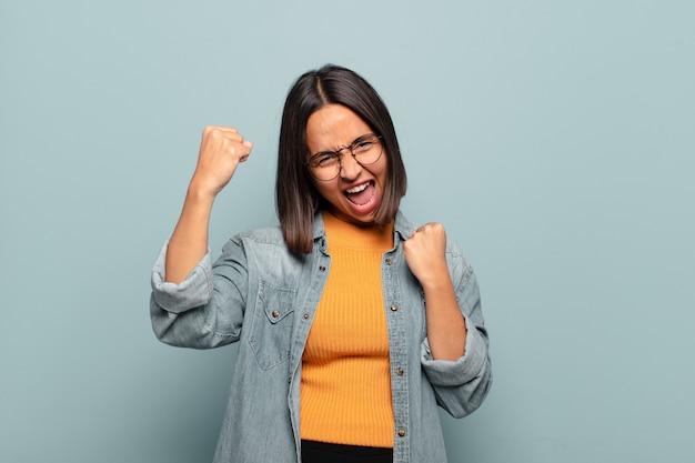Jonge spaanse vrouw triomfantelijk schreeuwen, kijkend als opgewonden, blij en verrast winnaar, vieren