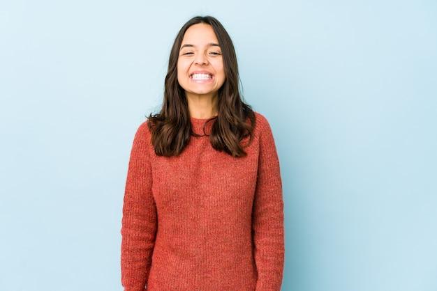 Jonge spaanse vrouw van gemengd ras lacht en sluit de ogen, voelt zich ontspannen en gelukkig.