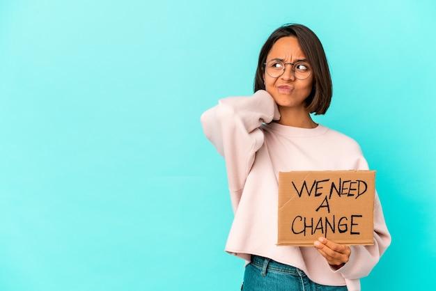 Jonge spaanse vrouw van gemengd ras met een inspirerend veranderingsbericht op karton dat de achterkant van het hoofd aanraakt, nadenkt en een keuze maakt.