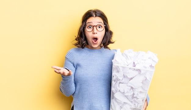 Jonge spaanse vrouw verbaasd, geschokt en verbaasd met een ongelooflijke verrassing faalt afvalconcept