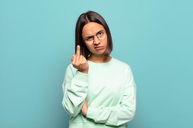 Jonge spaanse vrouw voelt zich boos, geïrriteerd, opstandig en agressief, draait de middelvinger om en vecht terug