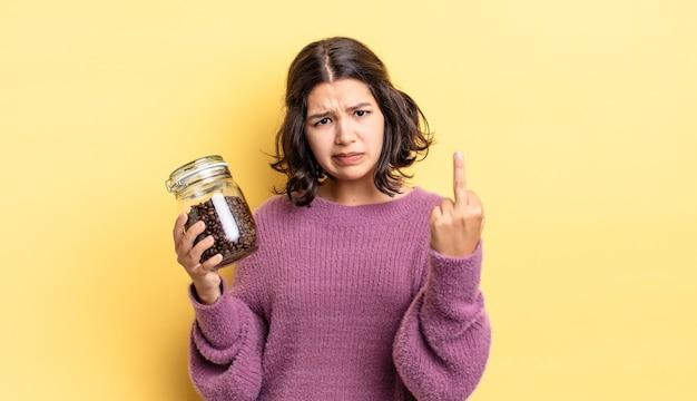 Jonge spaanse vrouw voelt zich boos, geïrriteerd, opstandig en agressief. koffiebonen concept