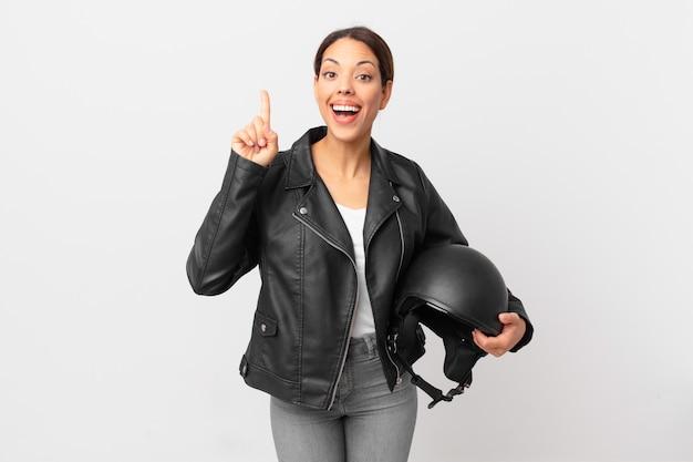 Jonge spaanse vrouw voelt zich een gelukkig en opgewonden genie nadat ze een idee heeft gerealiseerd. motorrijder concept