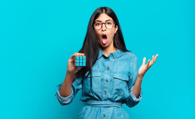 Jonge spaanse vrouw voelt zich extreem geschokt en verrast, angstig en in paniek, met een gestrest en geschokte blik. intelligentie probleem concept