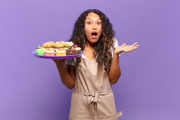 Jonge spaanse vrouw voelt zich extreem geschokt en verrast, angstig en in paniek, met een gestrest en geschokte blik. koken taarten concept